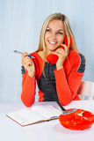 Beautiful smiling female holding phone and ballpoint pen Royalty Free Stock Image