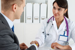 Beautiful smiling female medicine doctor shaking hands with male Royalty Free Stock Photos