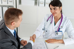 Beautiful smiling female medicine doctor shaking hands with male. Patient. Partnership, trust and medical ethics concept. Handshake with satisfied client Royalty Free Stock Image