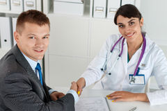 Beautiful smiling female medicine doctor shaking hands with male. Patient. Partnership, trust and medical ethics concept. Handshake with satisfied client Royalty Free Stock Photography