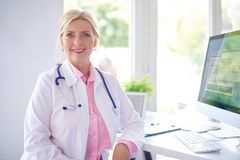 Female doctor portrait at the medical room. Beautiful smiling female research physician sitting in front of her computer at the doctor`s office and working stock images