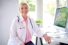 Female doctor portrait at the medical room. Beautiful smiling female research physician sitting in front of her computer at the doctor`s office and working royalty free stock image