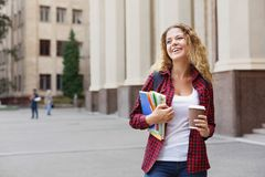 Beautiful female student standing in front of the university campus Stock Photos