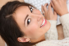 Beautiful smiling female student lying on wooden floor working Stock Image
