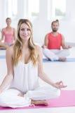 Beautiful smiling female yoga instructor. Beautiful female yoga instructor smiling at camera during yoga class Stock Image