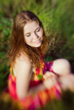 Beautiful smiling ginger girl with closed eyes sitting on grass. In summer park on sunny day. Selective focus on one eye, lensbaby blur effect. Relax and rest stock photos