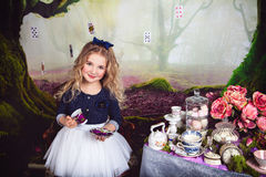 Beautiful smiling girl as Alice in Wonderland. Beautiful smiling girl in the image of Alice in Wonderland with a cup of tea in her hands royalty free stock photos