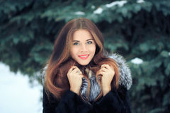 Beautiful smiling girl on background of snowy. Beautiful smiling girl on a background of trees. Winter portrait. coat with a hood Stock Photography