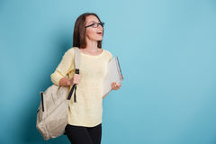 Beautiful smiling girl with bagpack and notebook over blue background Royalty Free Stock Photos