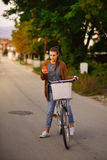 Beautiful smiling girl with a bicycle on the road Royalty Free Stock Photos