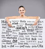 Beautiful smiling girl with a billboard of different languages Stock Image