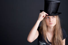 Beautiful smiling girl in a black hat. On a dark background Stock Image