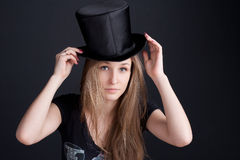 Beautiful smiling girl in a black hat. On a dark background Stock Photography