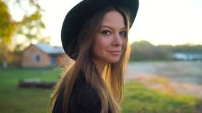 Beautiful smiling girl in a black hat with a sunset in the background walking outdoors. Slow motion. Beautiful smiling girl in a black hat with a sunset in the stock video footage