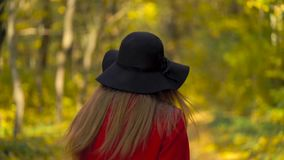 Beautiful smiling girl in a black hat with a yellow maple leaf in the background walking in the autumn forest stock video footage