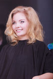 Beautiful smiling girl with blond wavy hair in hairdressing beauty salon Royalty Free Stock Photos