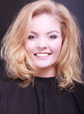 Beautiful smiling girl with blond wavy hair in hairdressing beauty salon. Beautiful smiling girl with blond wavy hair by hairdresser. Young woman in hairdressing Royalty Free Stock Photos