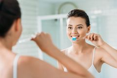 Beautiful smiling girl brushing teeth at mirror. In bathroom stock photography