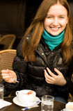 Beautiful smiling girl with a cup of cappuccino. In a Parisian street cafe Royalty Free Stock Photography