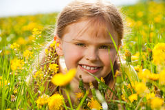 Beautiful smiling girl in dandelions portrait Stock Photo