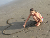 Beautiful smiling girl draws many hearts on the beach Stock Image
