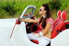 Beautiful smiling girl driving a white retro car Stock Photos