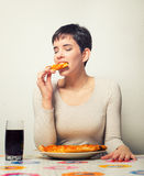 Beautiful smiling girl eating pizza and drinking coke at home Stock Image