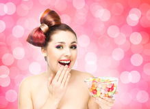 Beautiful smiling girl eating sweets from a bowl on blink background.  royalty free stock images