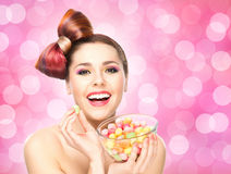 Beautiful smiling girl eating sweets. From a bowl on blink background stock image