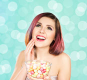 Beautiful smiling girl eating sweets from a bowl Royalty Free Stock Photos