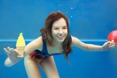 Beautiful smiling girl eating yellow ice cream underwater Royalty Free Stock Photos