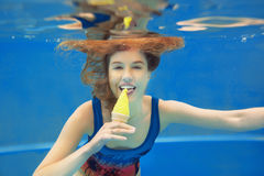 Beautiful smiling girl eating yellow ice cream underwater Stock Photos