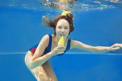 Beautiful smiling girl eating yellow ice cream underwater Royalty Free Stock Image