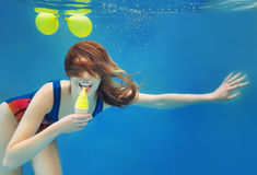 Beautiful smiling girl eating yellow ice cream underwater Royalty Free Stock Photo