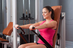 Beautiful smiling girl exercising arms on device Stock Photo