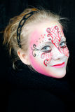 Beautiful smiling girl with face paint. Young woman with pink, red and black face paint with a very intense gaze Royalty Free Stock Image