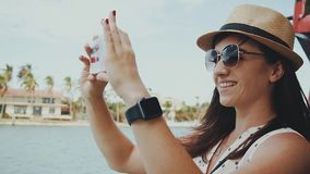 Beautiful smiling girl in glasses and hat making photo on phone on the background of tropical nature sunny isles beach stock video