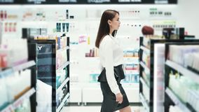 Beautiful girl goes among shelves in cosmetics shop, slow motion, steadicam shot. Beautiful smiling girl goes among shelves in cosmetics shop, slow motion stock footage