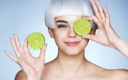 Beautiful smiling girl with halves of green lime. royalty free stock image