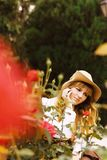 Beautiful girl in a hat in a vintage dress with roses. Summertime park. Lolita style stock images