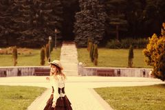 Beautiful girl in a hat in a vintage dress walking in a Summertime park. Lolita style stock images