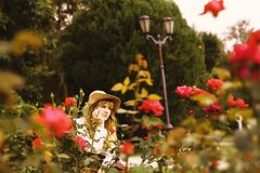 Beautiful girl in a hat in a vintage dress with roses. Summertime park. Lolita style royalty free stock photos