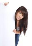 Beautiful smiling girl holding a blank billboard. Stock Image