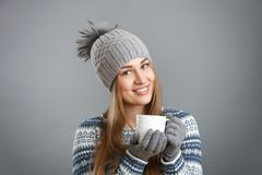 Beautiful smiling girl holding a cup with a hot drink. Attractive smiling girl holding a cup with a hot drink Royalty Free Stock Photography