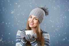 Beautiful smiling girl holding a cup with a hot drink. Attractive smiling girl holding a cup with a hot drink Royalty Free Stock Photo