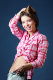 Beautiful smiling girl holds jeans by left hand Royalty Free Stock Image