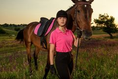 Beautiful smiling girl jockey stand next to her brown horse wearing special uniform on a sky and green field background Stock Photos