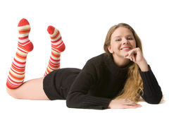 Beautiful smiling girl lies on the floor. Beautiful smiling girl in brown sweater and long red-orange socks lies on floor, isolated on white Royalty Free Stock Photos