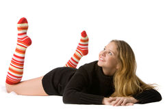 Beautiful smiling girl lies on the floor. Beautiful smiling girl in brown sweater and long red-orange socks lies on the floor and looks upward, isolated on white Stock Photography