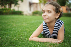 Beautiful smiling girl lies on green grass Royalty Free Stock Images